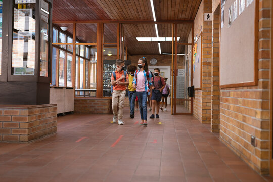 Group of diverse students wearing face masks walking in the corridor at school