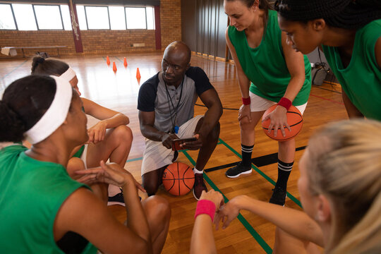 Diverse female basketball team and coach in huddle discussing game tactics