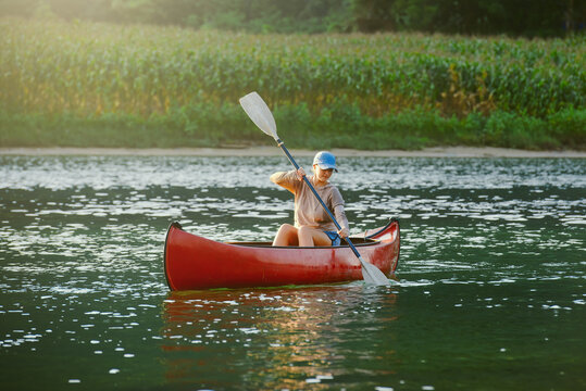 Woman on kayak swims on river in countryside.