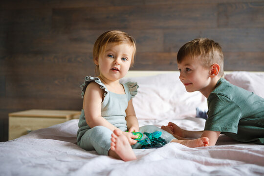 The little sister plays with her older brother at home.