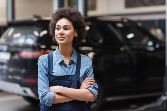 confident young african american mechanic in overalls standing with crossed arms in auto repair service