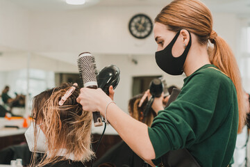 Fototapeta Hairdresser in a mask with at work, drying hair in a barbershop, client and stylist in masks. obraz