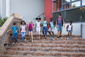 Obraz Group of diverse students with backpacks walking down the stairs together at school - fototapety do salonu