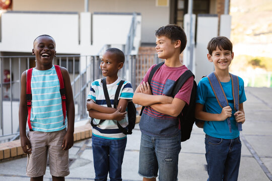 Group of diverse male students with backpacks smiling while standing at school