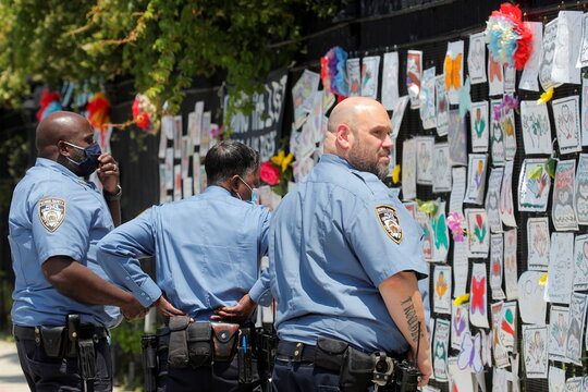 """Members of the NYPD School safety unit look at the """"Naming the Lost Memorials,"""" at The Green-Wood Cemetery in Brooklyn, New York"""