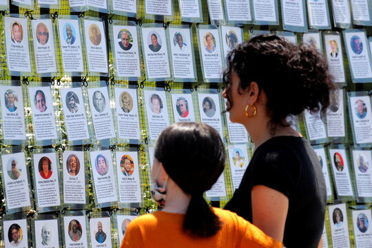 """A woman and child look at the """"Naming the Lost Memorials,"""" at The Green-Wood Cemetery in Brooklyn, New York"""