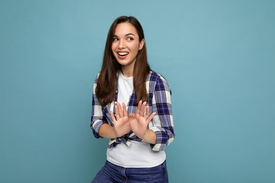 Young positive smiling beautiful brunette woman with sincere emotions wearing trendy check shirt standing isolated on blue background with empty space and showing stop gesture saying no