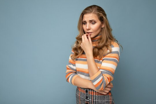 Photo portrait of young attractive beautiful sad upset thoughtful blonde woman with sincere emotions wearing striped sweater isolated on blue background with empty space and has doubts