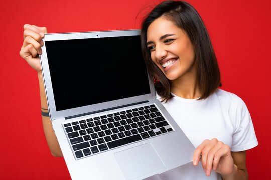 Photo of funny smiling Beautiful happy overjoyed young woman with short brunet hair holding computer laptop looking to the side wearing white t-shirt and jeans isolated over red wall background