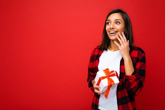 Photo shot of pretty positive surprised young brunet woman isolated over colourful background wall wearing trendy outfit look holding gift box and looking to the side