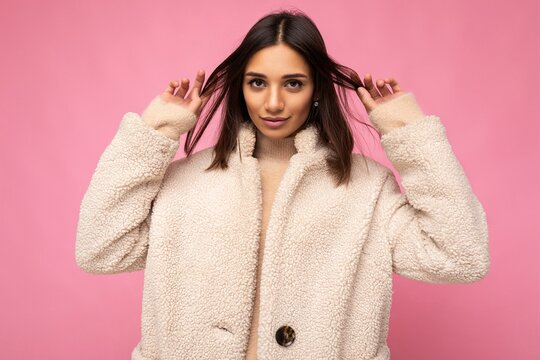 Portrait of attractive beautiful pretty self-confident positive good-looking stylish young brunette woman wearing autumn beaige warm coat isolated on pink background with free space. Fashion concept