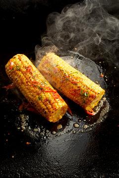 Tasty corn cobs preparing on hot surface