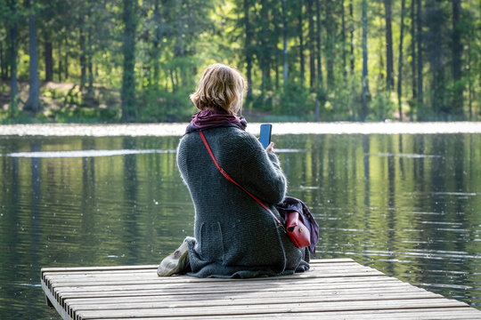 A young woman takes photos with a smartphone sitting on the wooden pier on a forest lake on a sunny summer day.