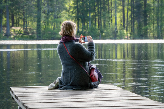 A woman takes photos with a smartphone sitting on the wooden pier on a forest lake on a sunny summer day.
