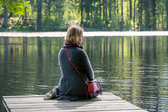 A young woman sits on the wooden pier on a forest lake on a sunny summer day.