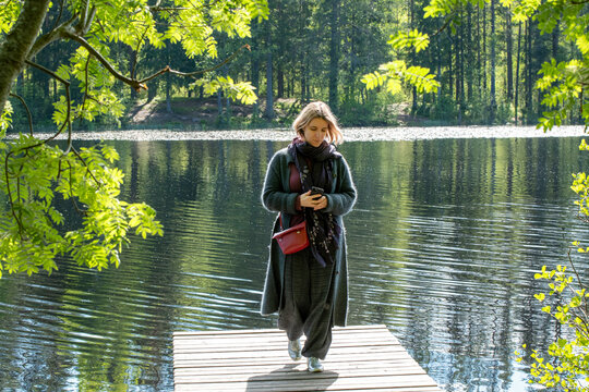A young woman walks along the wooden pieron a forest lake on a sunny summer day.