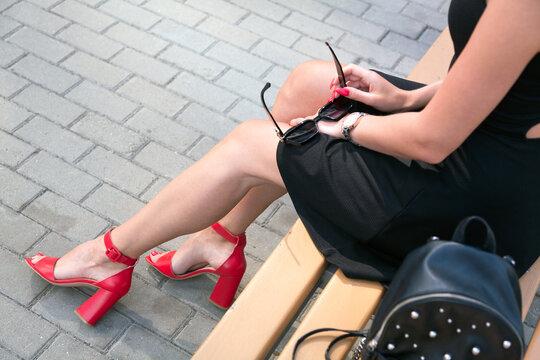 Long legged woman sitting on a bench