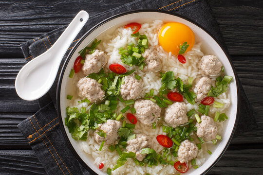 Diet rice soup with meatballs, lots of greens and an egg close-up in a bowl on the table. horizontal top view from above
