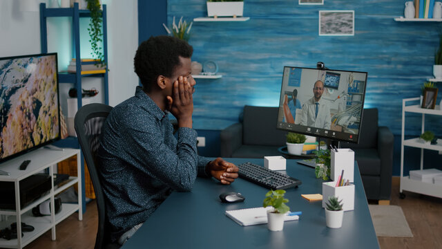 Black man with toothache seeking medical stomatologist health advice via internet video call communication. Online telehealth diagnose using webcam teethcare consultation, dental hygiene and
