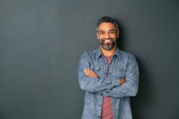Smiling mixed race mature man on grey background - fototapety na wymiar