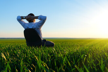 businessman sits in an office chair in a field and rests, freelance and business concept, green grass and blue sky as background - fototapety na wymiar