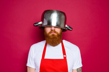 unhappy chef with beard and red apron plays with pot - fototapety na wymiar