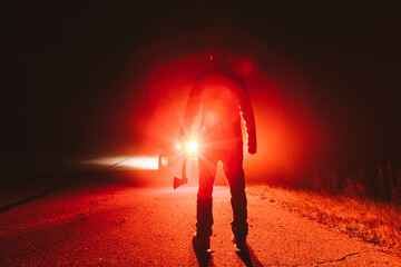 maniac killer near the car at night. silhouette of a man with an ax in his hand at night in a fog. - fototapety na wymiar