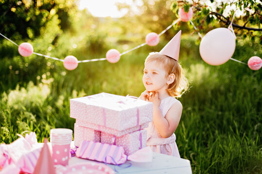 Happy birthday little girl with gift box in beautiful garden. child eat happy birthday rose cupcake. colorful pastel decoration outdoor. 4 years old kid celebrating enjoying party on summer day.