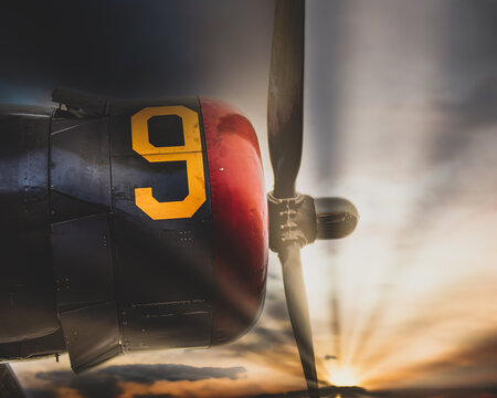 Vintage World War Two bomber airplane engine and propeller Sun low in the sky.