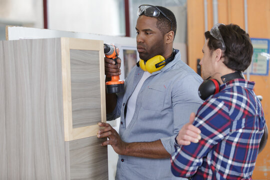supervisor watching apprentice doing practical carpentry training