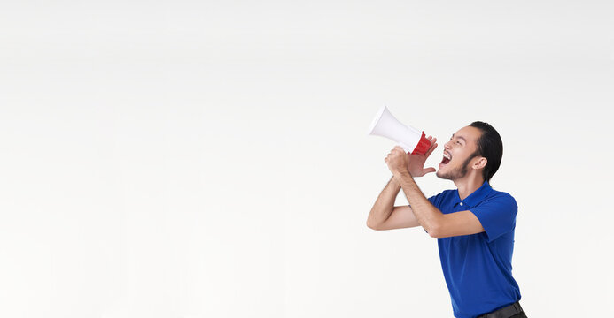 Happy young Asian man in blue shirt shouting announce into megaphone isolated on white background in studio.