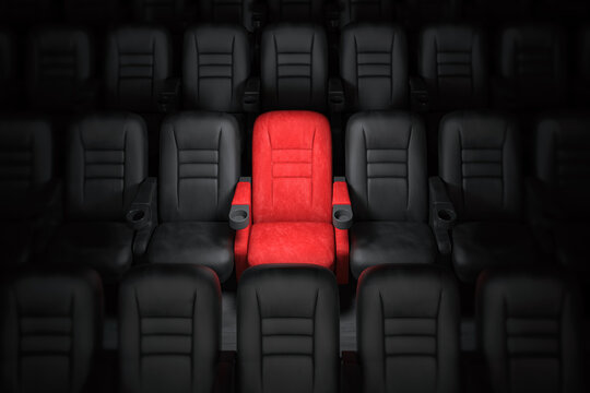 One red empty seat among others black seats in cinema hall.
