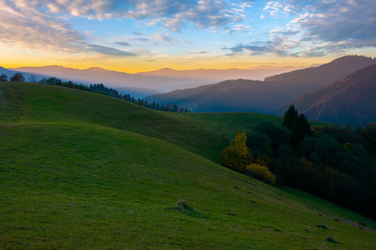 mountainous countryside at dawn. trees on hills and grassy meadows. ridge in the distance under the bright sky with clouds in evening light