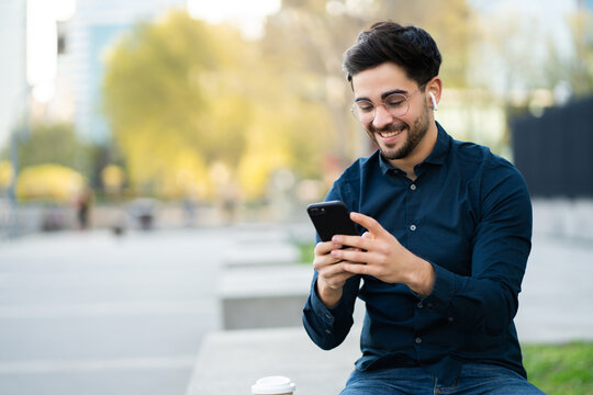 Young man using his mobile phone outdoors.