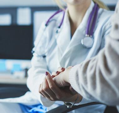 Doctor or nurse holding elderly lady's hands