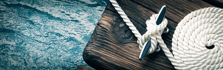 Close-up Of Coiled Boat Rope Secured To Cleat On Wooden Dock