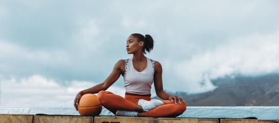 Fototapeta Athlete woman relaxing with basketball outdoors obraz