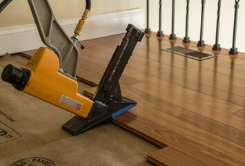 Nailing gun ready to staple sections of Brazilian Cherry tropical hardwood flooring in home renovation