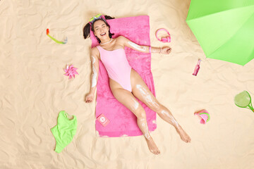 Obraz Cheerful Asian female model wears snorkeling mask pink swimsuit has upbeat mood applies suncream poses over white sand at beach surrounded by different necessary items. Summer lifestyle concept - fototapety do salonu