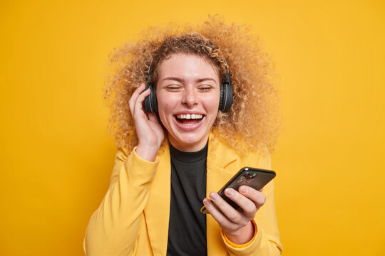 Overjoyed sincere young woman enjoys listening music via headphones keeps eyes closed holds mobile phone expresses authentic haappy emotions forgets about all troubles has natural curly hair