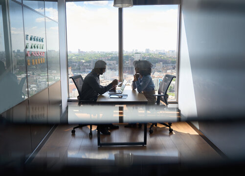 Young indian businessman ceo hr director having interview hiring for job with female African American attorney sitting in office at panoramic view window. Shot through jalousie glass.