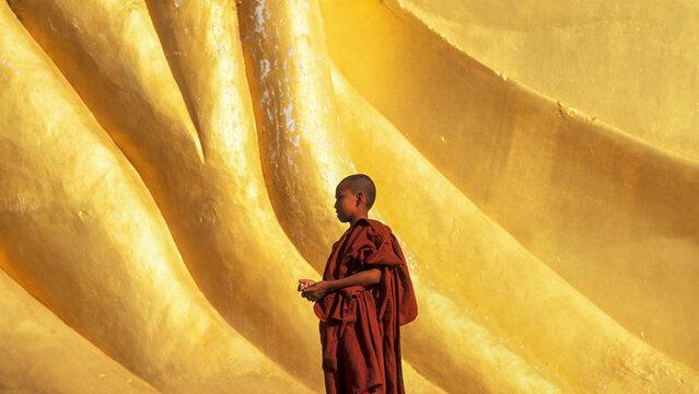 Myanmar, Monyma, Mandalay Division, Novice monk praying under giant statue of reclining Buddha in Lay Kyune Sakkyar temple