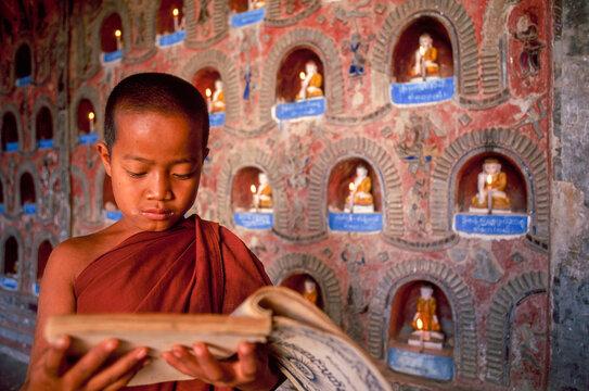 Myanmar, Shan State, Inle Lake, Novice Buddhist monk reading prayers in Shwe Yan Pyay Monastery