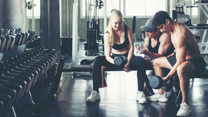 Trainer training exercise with man and woman at the gym for healthy care and body slim.  Fitness instructor exercising with his client people the fitness. Diet and Healthy sport Concept - fototapety na wymiar