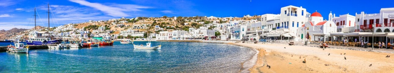 Mykonos island. Greece summer holidays. Panorama of old port in downtown. view with boats bars and restaurants. Cyclades. June 2021