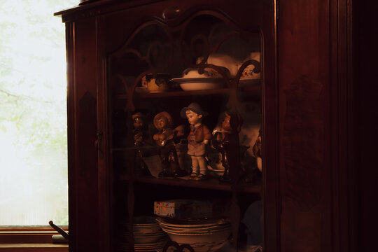 Retro Western dolls wooden shelf with antique cutleries, tea cups and plates