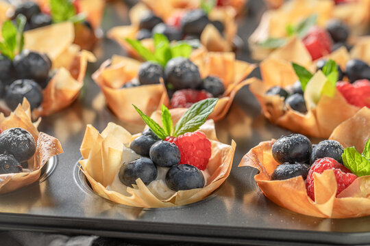 Homemade phyllo cups with berries and cream. Summer snack.