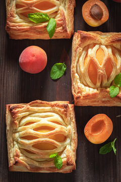 Sweet puff pastry with sugar and peaches. French juicy dessert.