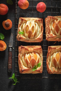 Tasty puff pastry with sugar and peaches. Unique yummy cake.