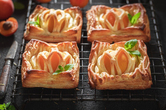 Sweet puff pastry with peaches and mint. French juicy dessert.
